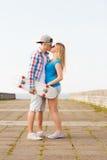 Ajouter de sourire à la planche à roulettes embrassant dehors Photos libres de droits