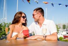 Ajouter de sourire au champagne et au cadeau au café Photographie stock