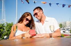 Ajouter de sourire au champagne et au cadeau au café Photo libre de droits