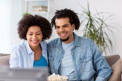 Ajouter de sourire au maïs éclaté regardant la TV à la maison Photo stock