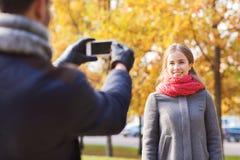 Ajouter de sourire au smartphone en parc d'automne Photographie stock libre de droits