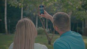 Ajouter de sourire au téléphone portable prenant le selfie en parc banque de vidéos