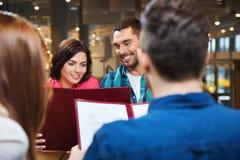 Ajouter de sourire aux amis et menu au restaurant Image stock