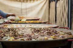 Ajouter des fruits de mer aux poêles énormes Les gens préparent une Paella géante images stock