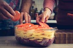 Ajouter des tomates dans le plat de cuisson avec de la viande crue et des pommes de terre Photographie stock libre de droits