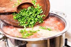 Ajouter des verts coupés au potage aux légumes Image libre de droits