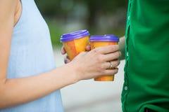 Ajouter fiancés aux tasses de café dans des mains, marchant en parc Images libres de droits