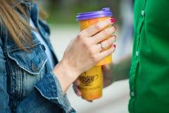 Ajouter fiancés aux tasses de café dans des mains, marchant en parc Photo libre de droits