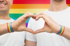 Ajouter gais aux bracelets d'arc-en-ciel et au coeur de main Photo libre de droits