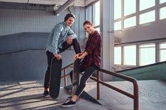 Ajouter gais de la jeunesse aux planches à roulettes portant les vêtements sport posant à côté d'un rail de morcellement dans le  photos libres de droits