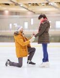 Ajouter heureux à la bague de fiançailles sur la piste de patinage Photo libre de droits