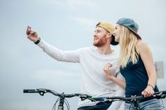 Ajouter heureux à la bicyclette prenant le selfie dehors Images stock