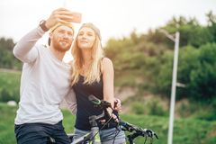 Ajouter heureux à la bicyclette prenant le selfie dehors Photo libre de droits