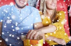 Ajouter heureux au maïs éclaté dans la salle de cinéma Photo stock