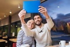 Ajouter heureux au PC de comprimé prenant le selfie au café Photo stock
