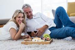 Ajouter heureux au vin rouge et à la nourriture tout en se trouvant sur la couverture Images stock