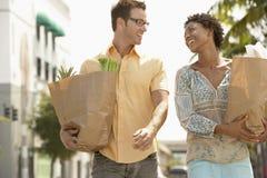 Ajouter heureux aux épiceries marchant dehors Image stock