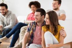 Ajouter heureux aux amis regardant la TV à la maison Photographie stock