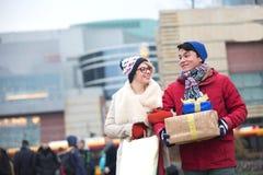 Ajouter heureux aux cadeaux et aux paniers marchant dans la ville pendant l'hiver Image stock