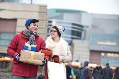 Ajouter heureux aux cadeaux et aux paniers marchant dans la ville pendant l'hiver Photos libres de droits