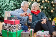 Ajouter heureux aux présents se reposant dans Noël Photo libre de droits