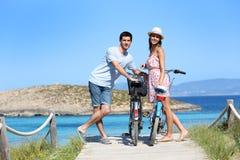 Ajouter heureux aux vélos se tenant prêt le rivage Photographie stock libre de droits