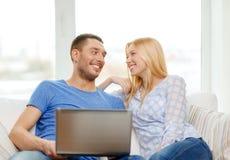 Ajouter heureux de sourire à l'ordinateur portable à la maison Photographie stock