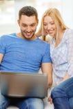 Ajouter heureux de sourire à l'ordinateur portable à la maison Image libre de droits