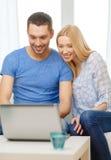 Ajouter heureux de sourire à l'ordinateur portable à la maison Photographie stock libre de droits