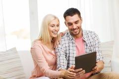 Ajouter heureux de sourire au PC de comprimé à la maison photographie stock libre de droits