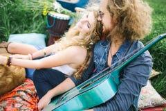 Ajouter hippies assez bouclés de jeunes à la guitare extérieure Photographie stock