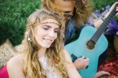 Ajouter hippies assez bouclés de jeunes à la guitare extérieure Image libre de droits