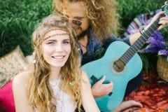 Ajouter hippies assez bouclés de jeunes à la guitare extérieure Photo libre de droits