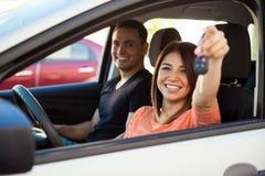 Ajouter hispaniques à une nouvelle voiture Photographie stock libre de droits