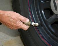 Ajouter l'air à un pneu d'automobile Photographie stock libre de droits