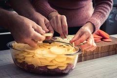 Ajouter l'oignon dans le plat de cuisson avec de la viande crue et des pommes de terre Images libres de droits