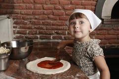 Ajouter la sauce au ` s de tomate à la pizza Photographie stock libre de droits
