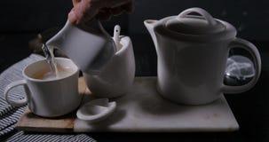 Ajouter le lait à une tasse chaude de cuisson à la vapeur intéressante de thé banque de vidéos