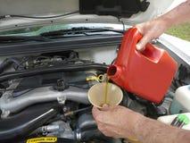 Ajouter le pétrole de moteur au véhicule Photo libre de droits