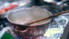 Ajouter le vin rouge et le lait au ragoût de homard banque de vidéos