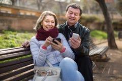 Ajouter mûrs aux smartphones sur le banc de parc Photo stock