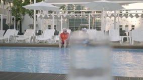 Ajouter mûrs heureux d'amusement à peu de petite-fille s'asseyant au bord de la piscine de luxe Grand-mère, grand-père et clips vidéos