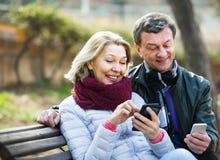 Ajouter mûrs aux smartphones en parc Photographie stock libre de droits