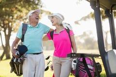 Ajouter mûrs gais de golfeur au bras autour Photo stock