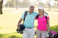 Ajouter mûrs heureux de golfeur au bras autour Photo stock
