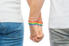 Ajouter masculins aux bracelets d'arc-en-ciel de fierté gaie Photo libre de droits