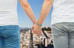 Ajouter masculins aux bracelets d'arc-en-ciel de fierté gaie Photographie stock