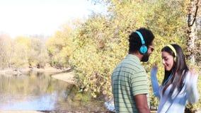 Ajouter mignons aux écouteurs écoutant la musique et dansant par le lac banque de vidéos