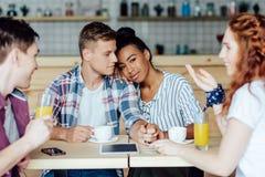 Ajouter multi-ethniques aux amis en café Images libres de droits