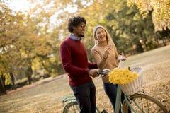 Ajouter multiraciaux à la bicyclette en parc d'automne photographie stock libre de droits
